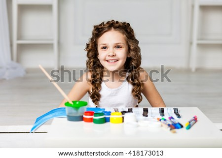 Little cute curly girl draws paints in an album, there are a number jars with paints, markers, hairstyle with two pigtails girl plays pranks, naughty, laughs, smiles - stock photo