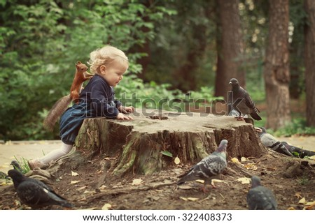 Little cute elegant beautiful girl walks in autumn park and feeding pigeons and squirrels - stock photo