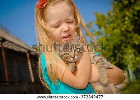 Little cute girl affectionately hugging small kitten. Children play outdoors in summer. Portrait happy child and dreams outdoors against the blue sky. - stock photo