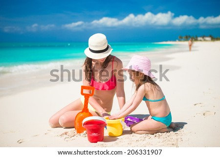 Little cute girl and young mother building sandcastle at tropical beach - stock photo