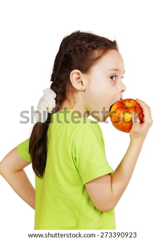 Little cute girl bites a big red apple. View of profile - stock photo