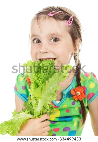 Little cute girl bites green leaf lettuce - stock photo