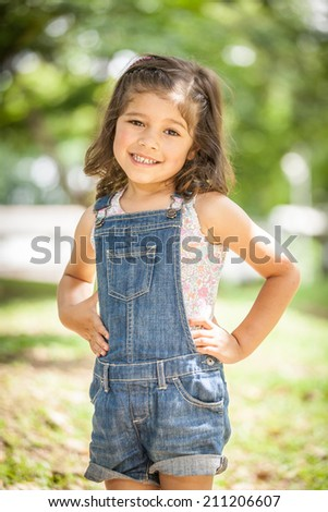 Little cute girl dressing jean smiling in nice garden background - stock photo