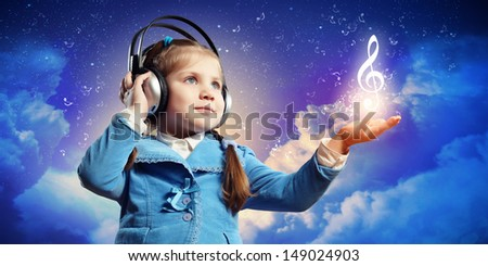 Little cute girl in headphones enjoying music - stock photo