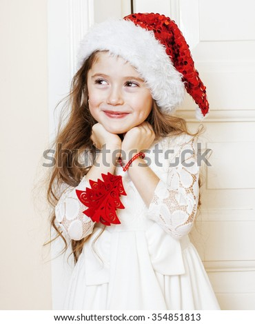 little cute girl in santas red hat waiting for Christmas gifts. smiling adorable kid. White new dress home interior close up - stock photo