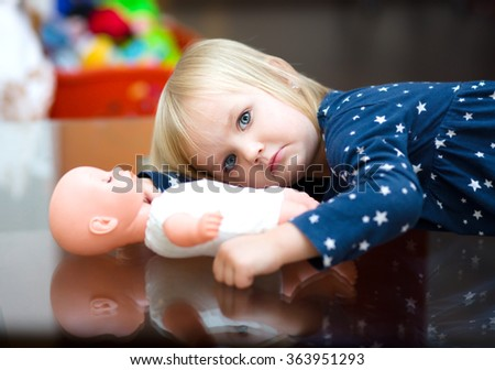Little cute girl is daydreaming, holding a doll - stock photo