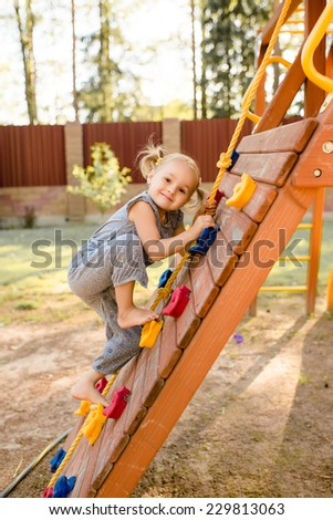 Little cute girl is playing on playground. - stock photo