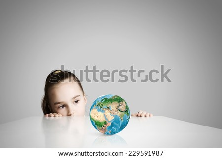 Little cute girl looking at globe. Elements of this image are furnished by NASA - stock photo
