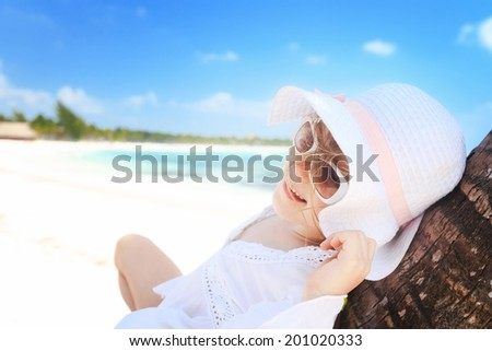 little cute girl lying on palm tree at the perfect beach - stock photo