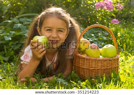 Little cute girl lying on the grass in the garden and eating fresh green apple - stock photo