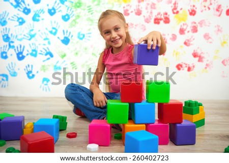 Little cute girl making pyramid of colored cubes and looking at the camera. Preschool center for children - stock photo