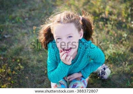Little cute girl on the lawn in the grass Little cute girl on the lawn on the grass showing its teeth funny - stock photo
