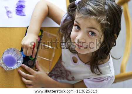 Little cute girl painting with brush inside in preschool. Child care. - stock photo