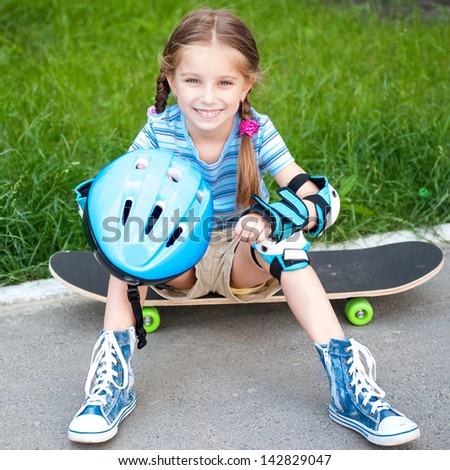 little cute girl sitting on a skateboard in the park - stock photo