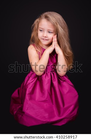 Little cute girl sitting on the floor in a pink dress on a black background in the studio - stock photo
