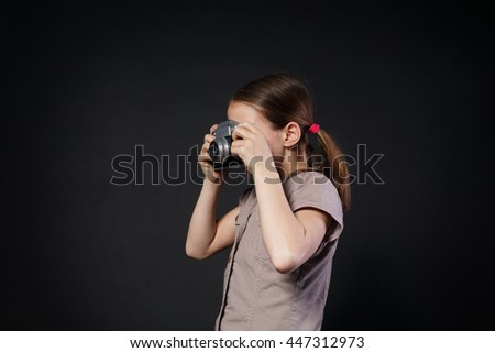 Little cute girl take photo with old vintage film camera at black background. Small female child photographer makes photograph. - stock photo