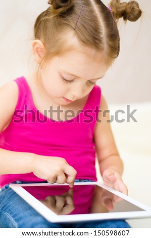 little cute girl using tablet computer at home - stock photo