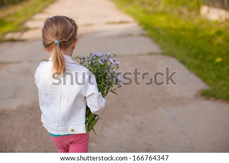 Little cute girl walking with a bouquet of flowers - stock photo