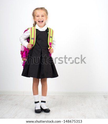 little cute girl with a backpack on a white background - stock photo
