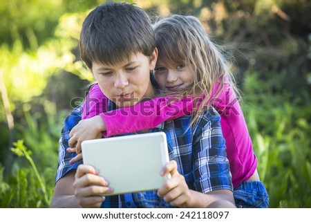 Little cute girl with an older brother holding the tablet, outdoors. - stock photo