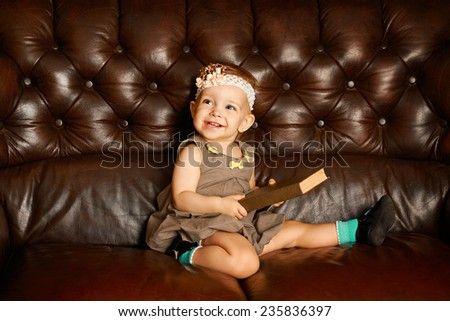 Little cute girl with big book sitting on a leather couch - stock photo