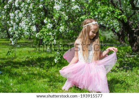 Little cute girl with butterfly wings in blossoming apple orchard - stock photo