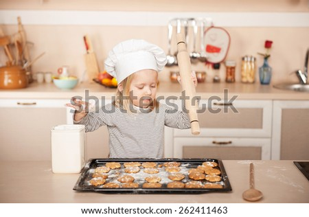 Little cute girl with chef hat and rolling pin preparing cookies. Kitchen interior. Concept for young kitchen hands - stock photo