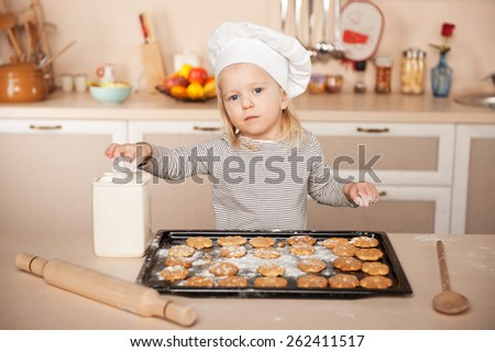 Little cute girl with chef hat looking at camera and preparing cookies. Kitchen interior. Concept for young kitchen hands - stock photo