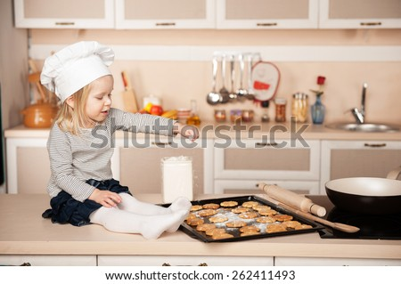 Little cute girl with chef hat preparing cookies. Kitchen interior. Concept for young kitchen hands - stock photo