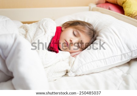 Little cute girl with cold sleeping under blanket - stock photo