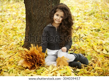 little cute girl with dark curly hair sitting in the autumn forest with a bouquet of leaves - stock photo