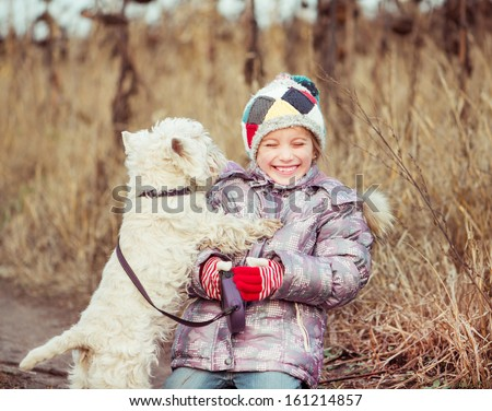 little cute girl with her dog breed White Terrier  in a field in autumn - stock photo