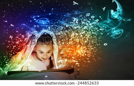 Little cute girl with in bed reading book under blanket - stock photo