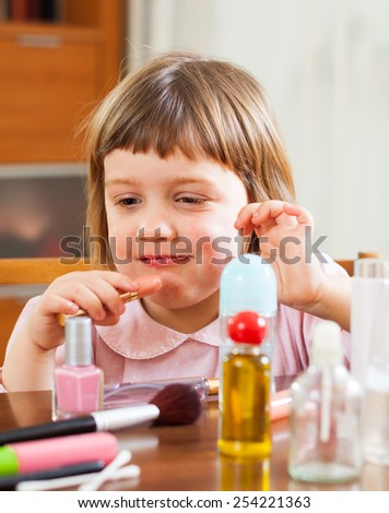 Little cute girl  with  mom's lipstick - stock photo