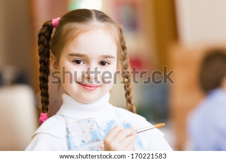 Little cute girl with paint brush and easel - stock photo