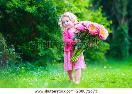 Little cute girl with peony flowers. Child wearing a pink dress playing in a summer garden. Kids gardening. Children play outdoors. Toddler kid with flower bouquet for birthday or mother's day. - stock photo