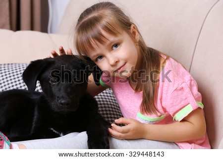 Little cute girl with puppy on sofa at home - stock photo
