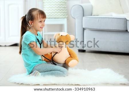 Little cute girl with stethoscope and teddy bear sitting on carpet, on home interior background - stock photo