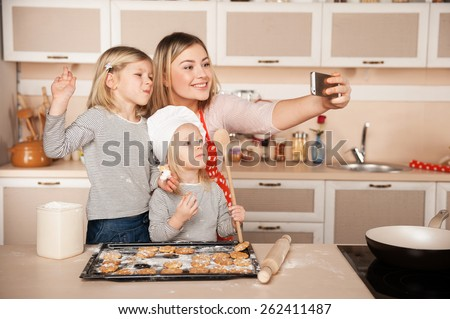 Little cute girls and their mother making photo while preparing cookies. Kitchen interior. Concept for young kitchen hands - stock photo