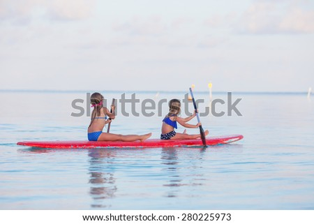 Little cute girls swimming on surfboard during summer vacation - stock photo