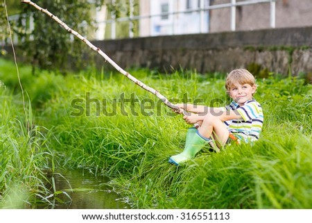 Little cute kid boy fishing on a river with selfmade fishing rod  on sunny summer day. Happy child having fun. Active leisure for children outdoors. - stock photo