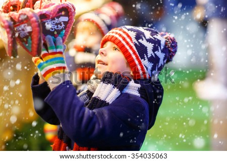 """Little cute kid boy happy about gingerbread cookies hearts. Happy child on Christmas market in Germany. Traditional leisure for families on xmas. """"happy Holiday"""" on gingerbread. - stock photo"""