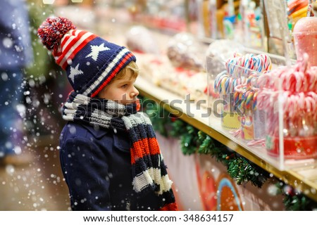 Little cute kid boy near sweet stand with candy canes. Happy child on Christmas market in Germany. Traditional leisure for families on xmas - stock photo
