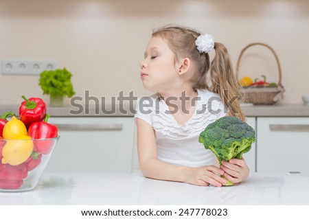 Little cute preschool girl in the kitchen refuses to eat broccoli - stock photo