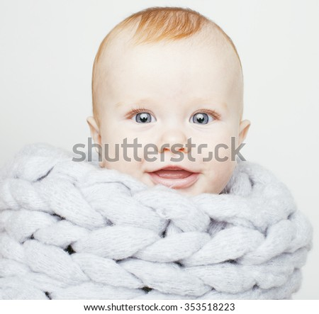 little cute red head baby in scarf all over him close up isolated, adorable kid winter clothers smiling - stock photo