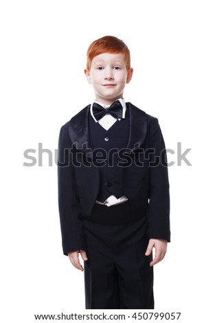 Little cute redhead boy in tailcoat tuxedo pose standing still. Portrait of well-dressed child in bow tie isolated on white background - stock photo