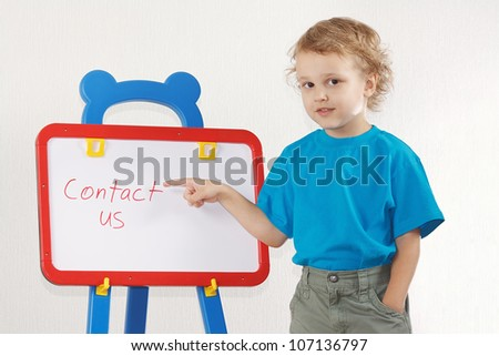 Little cute smiling boy shows the word contact us on a whiteboard - stock photo