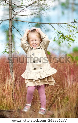 little cute smiling girl in beige coat is standing in the field and holding her hat on the head - stock photo