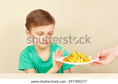 Little cute unhappy boy refuses to eat a french fries - stock photo