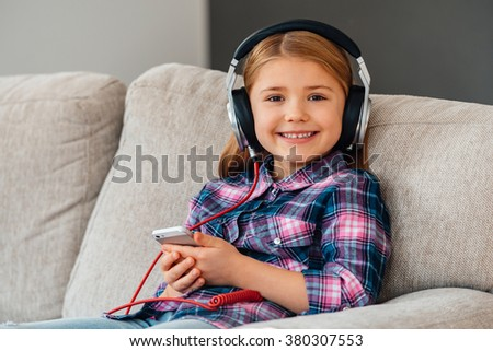 Little cutie loves music. Cheerful little girl in headphones holding smart phone and looking at camera with smile while sitting on the couch at home - stock photo